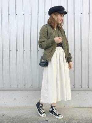カーキのブルゾンに白のフレアスカートを合わせた女性