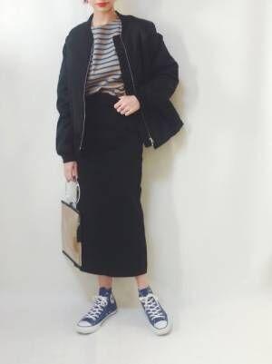 ボーダートップスに黒のタイトスカートを合わせて、黒のブルゾンを羽織った女性