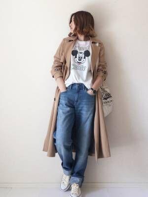 ミッキーTシャツにデニムパンツ、トレンチコートを羽織ったコーデ