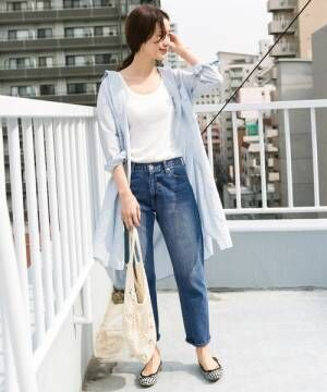 白Tにデニムパンツを履きシャツを羽織った女性