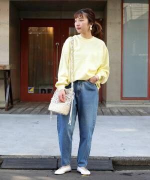 黄色のトップスにデニムを合わせて白いフラットシューズを履いた女性