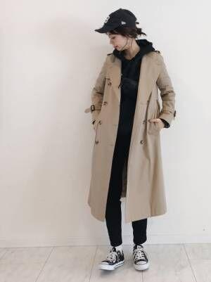 黒のパーカー、黒のスキニーパンツにベージュのトレンチコートを着た女性
