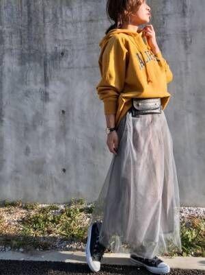 黄色のロゴパーカーにグレーのチュールスカートを履いた女性