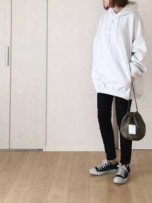 白のパーカーに黒のスキニーパンツを履いた女性