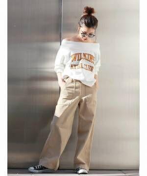 白いロゴトップスにチノパンを合わせてスニーカーを履いた女性