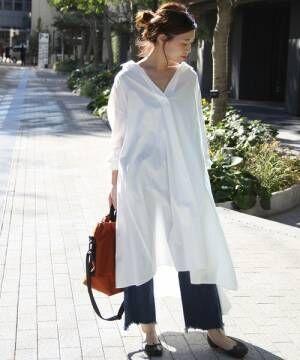 白いシャツワンピにデニムを合わせて黒いバレエシューズを履いた女性