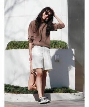 ブラウンのトップスに白いハーフパンツを合わせて黒いスニーカーを履いた女性