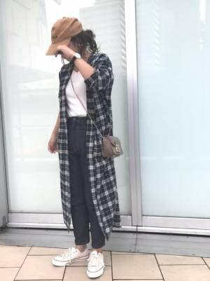 白いトップスにデニムを合わせてチェックのロングシャツを羽織った女性
