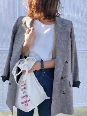 白いTシャツにデニムパンツを合わせてチェックのジャケットを羽織った女性