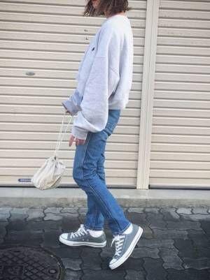 スウェットにデニムを合わせてスニーカーを履いた女性