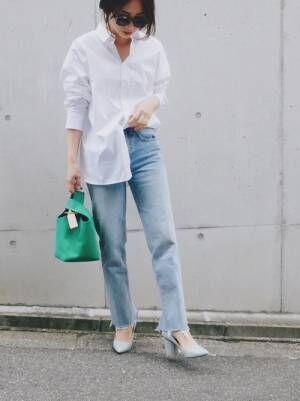 白いシャツにデニムパンツを合わせてグリーンのバッグを持った女性