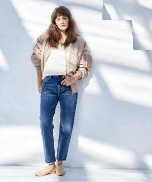 デニムパンツにベージュブルゾンを着た女性