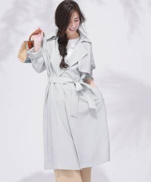 白トップスとベージュパンツにグレートレンチコートを着た女性