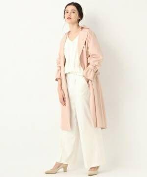 オールホワイトコーデにピンクトレンチコートを着た女性