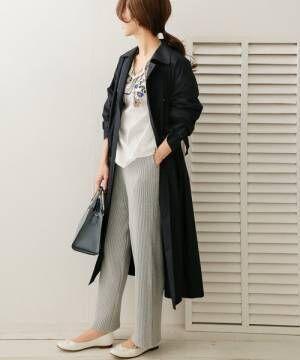 グレーニットパンツにネイビートレンチコートを着た女性