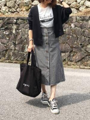 ロゴTシャツに黒のカーディガンを羽織って、ストライプ柄のタイトスカートを合わせた女性