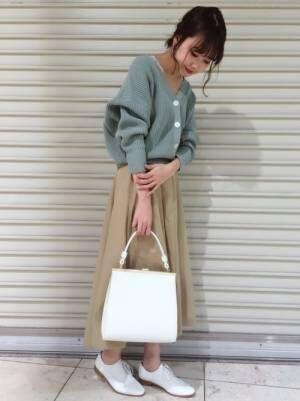 グリーンのショート丈カーディガンにベージュのスカートを合わせた女性