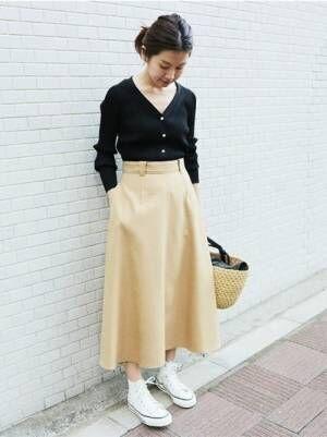 黒のショート丈カーディガンの前をしめて、ベージュのスカートを合わせた女性