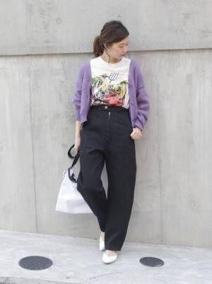 白のプリントTシャツにパープルのショート丈カーディガンを羽織って黒のパンツを合わせた女性