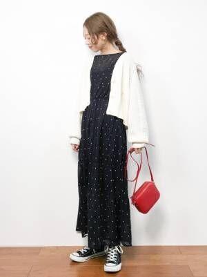 ドット柄のワンピースに白のショート丈のカーディガンを羽織った女性