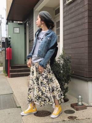 グレーのスウェットに花柄のスカートを合わせてイエローのスニーカーを履いた女性