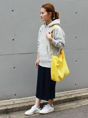 グレーのパーカーに黒いスカートを合わせてイエローのバッグを持った女性