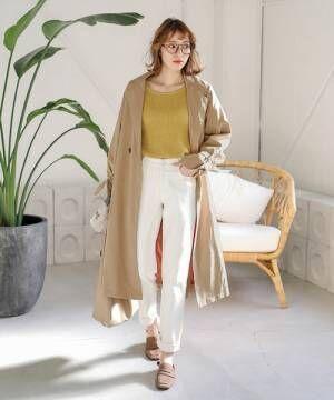 イエローニットに白いパンツを合わせてトレンチコートを羽織った女性