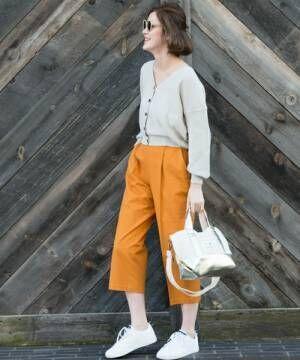 ニットカーデにイエローのパンツを合わせて白いスニーカーを履いた女性