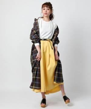 白いトップスにイエローのスカートを合わせてチェックのガウンを羽織った女性