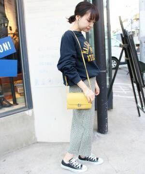 ロゴスウェットにギンガムチェックのスカートを合わせてイエローのバッグを持った女性