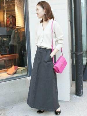白いカーディガンに黒いスカートを合わせてピンクのバッグを持った女性