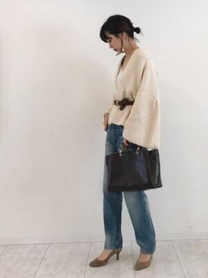 白いカーディガンにデニムを合わせて黒いバッグを持った女性