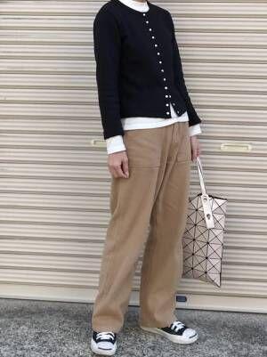 黒いカーディガンにチノパンを合わせて黒いスニーカーを履いた女性