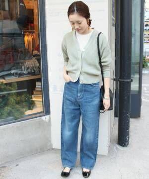 ミントグリーンのカーデにTシャツを合わせてデニムを履いた女性