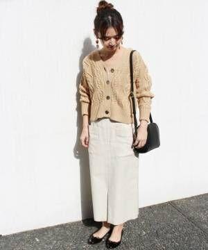 ベージュのカーディガンに白いスカートを合わせて黒いバレエシューズを履いた女性