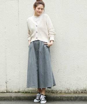 白いカーディガンにフリルのトップスを合わせてデニムスカートを履いた女性
