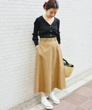 黒いカーディガンにベージュのスカートを合わせて白いスニーカーを履いた女性