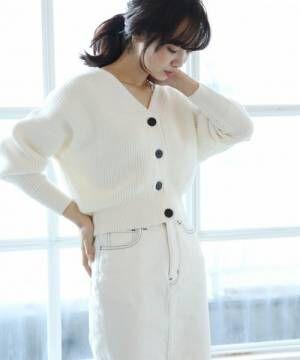 白カーディガンに白スカートを履いた女性
