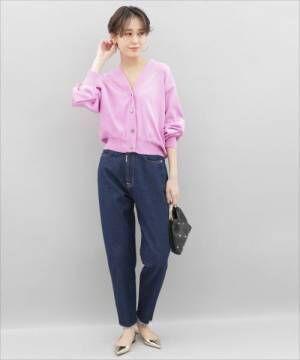 ピンクのカーディガンにデニムを合わせてメタリックのバレエシューズを履いた女性