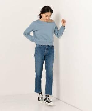 ブルーのトップスにデニムを合わせてスニーカーを履いた女性