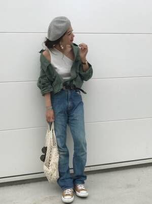 白いタンクトップにカーキのシャツを合わせてデニムを履いた女性