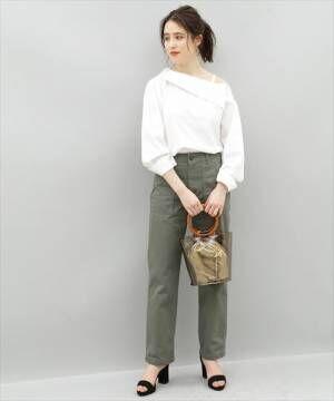 白いブラウスにカーキのパンツを合わせてビニールのバッグを持った女性