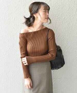 ブラウンのワンショルダーニットにスカートを履いた女性