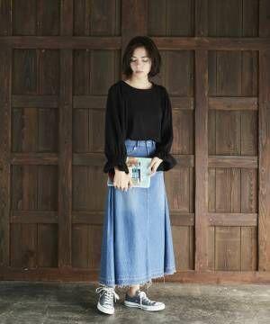 黒ブラウスにデニムスカートを合わせてスニーカーを履いた女性