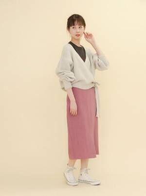 カシュクールニットにピンクのスカートを合わせて白いスニーカーを履いた女性