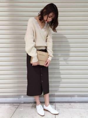 白いニットにブラウンのスカートを合わせて白いおじ靴を履いた女性