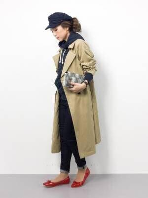 ネイビーのパーカー、デニムパンツにベージュのトレンチコートを着た女性