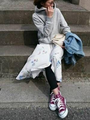 白の花柄ワンピース、グレーのパーカーに黒のパンツを履いた女性