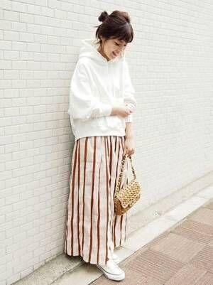 白のパーカーにストライプスカートを履いた女性