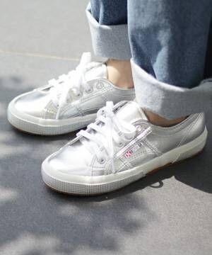 デニムパンツにスペルがの白スニーカーを履いた女性